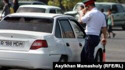 Сотрудник полиции подходит к остановленному им автомобилю.