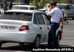 Көліктің қасында тұрған жол полициясы өкілі.