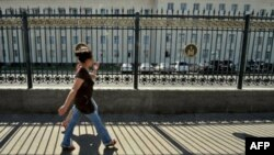 Молодые люди проходят мимо здания парламента в столице Моноголии Улан-Баторе.