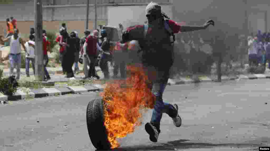 A Palestinian protester kicks a burning tire during clashes between Palestinian stone-throwers and Israeli security forces outside Ofer prison near the West Bank city of Ramallah. (Reuters/Mohamad Torokman)