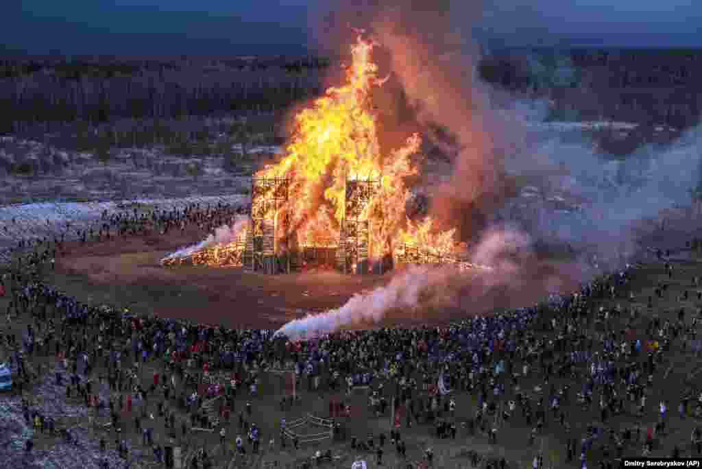 People watch a sculpture of a bridge burning at the Nikola-Lenivets art park about 200 kilometers southwest of Moscow on February 29.