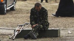 Поранені український військовослужбовець курить на подвір'ї військово-польового шпиталю у місті Сватове