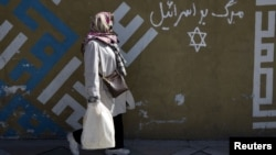 "A woman walks past writing on a wall in Persian that says ""Down with Israel"" in northern Tehran."