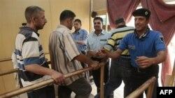 A security guard frisks visitors entering Baghdad's Imam Musa al-Kadhim shrine on July 27