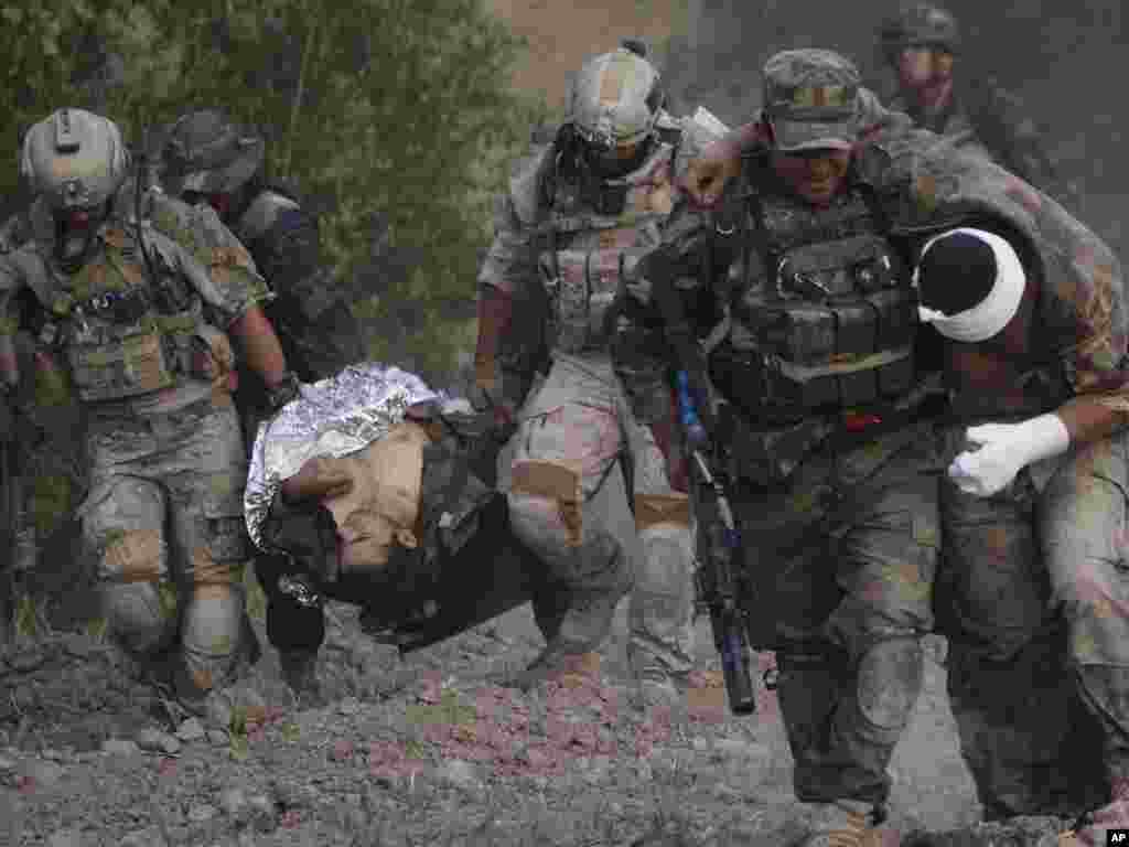 An Afghan National Army soldier carries a wounded colleague as U.S. troops carry another wounded Afghan soldier to a medical-evacuation helicopter following a roadside bomb attack on the outskirts of Kandahar, Afghanistan, on July 29. Photo by Rafiq Maqbool for AP