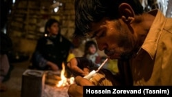 Iran -- A drug addict in Sistan & Balouchestan province using drugs in front of his family. December 20, 2015.