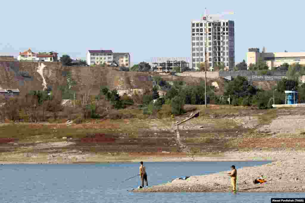 Men fishing in the shallow water of the Simferopol Reservoir. Authorities in Sevastopol have warned that the city's water supplies will run out in three months. One plan calls for building a pipeline to transfer water from the Kadykovsky quarry to the Simferopol Reservoir.