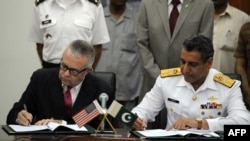 Deputy U.S. Ambassador in Islamabad Richard Hoagland (left) and the head of Pakistani delegation, Rear Admiral Farrukh Ahmed, sign the supply agreement in the Pakistani Defense Ministry in Rawalpindi on July 31.