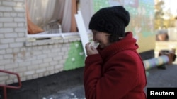 A woman cries outside a local kindergarten that was damaged by the explosions at the military depot in Svatove.