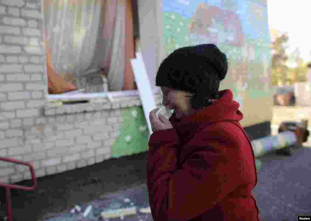 Жінка плаче біля будівлі дитсадка, який був пошкоджений в результаті вибухів на військовому складі у Сватові