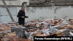 Эдем Дудаков возле поддонов с черепицей, снятой с кровли Ханской мечети. 22 февраля 2018 года