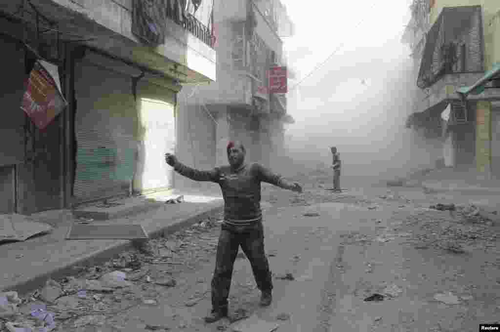 An injured man walks along a street after what activists said was a barrel bomb dropped by forces loyal to Syria's President Bashar al-Assad in Aleppo's al-Myassar neighbourhood on April 16. (Reuters/Firas Badawi)