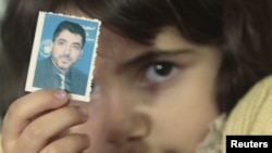 A family member of Dirar Abu Sisi holds his picture at his home in Gaza City.