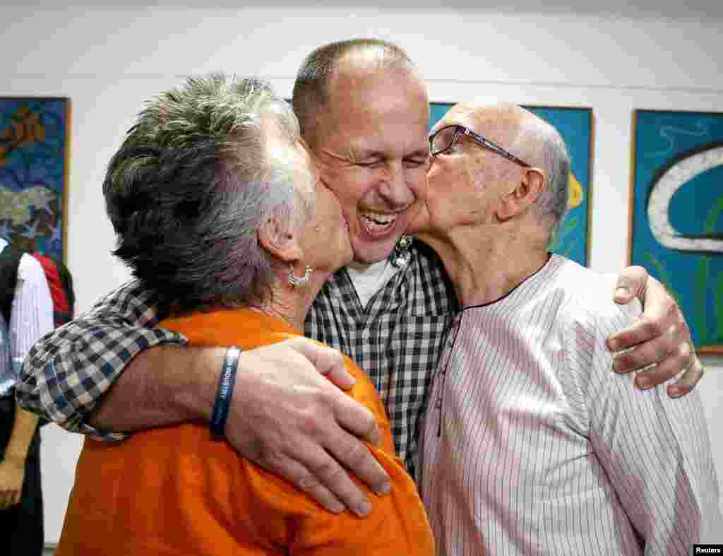 Australian journalist Peter Greste (center) receives a kiss from his mother, Lois, and father, Juris, upon his return home at Brisbane International Airport. Greste, the Al-Jazeera journalist freed after more than a year in an Egyptian prison, arrived back in his Australian homeland on February 5 and called for the release of two colleagues still in custody. (Reuters/Nathan Richter)