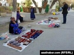 Женщина продает на улице изделия с туркменским орнаментом. Иллюстративное фото.