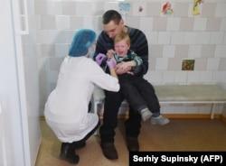 Киевская медсестра делает прививку ребенку