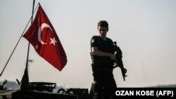 Аскердик танктын үстүндө турган түрк полицейи. Стамбул, Түркия.