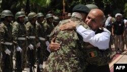 افغان ولسمشر محمد اشرف غني له افغان سرباز سره په غېږ روغبړ کوي.