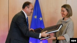 Kosovski šef diplomatije Enver Hodžaj i evropska komesarka Federika Mogerini razmenjuju dokumente posle potpisivanja Sporazuma za učešće Kosova u programima EU, Brisel