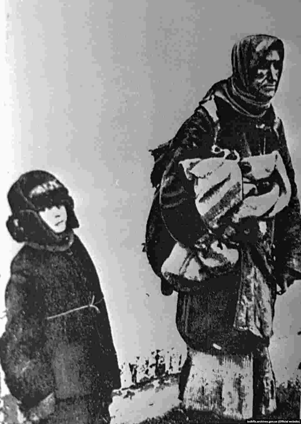 Жінка з дитиною ідуть з села у пошуках їжі. Місце і дата зйомки: УССР, 1932-1933 рр