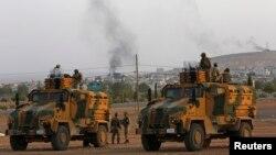 Pamje e ushtarëve të Turqisë në makinat e tyre ushtarake, ndërsa në plan të dytë shihet qyteti kufitar Kobani