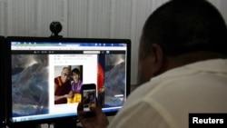 Китайский диссидент Ай Вэйвэй фотографирует на мобильный телефон фото Далай Ламы и демократического лидера Мьянмы Аун Сан Су Чжи у себя в студии. Пекин, 20 июня 2012 года.