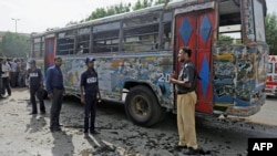 A policeman and volunteers stand in front of a damaged bus after a bomb explosion in Karachi on August 17.