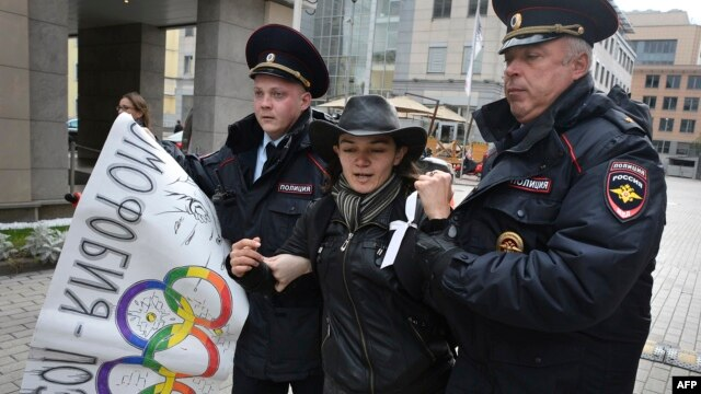 Moscow police detain a rights activist during a protest against a ban on staging a gay pride parade during the Sochi Olympics.