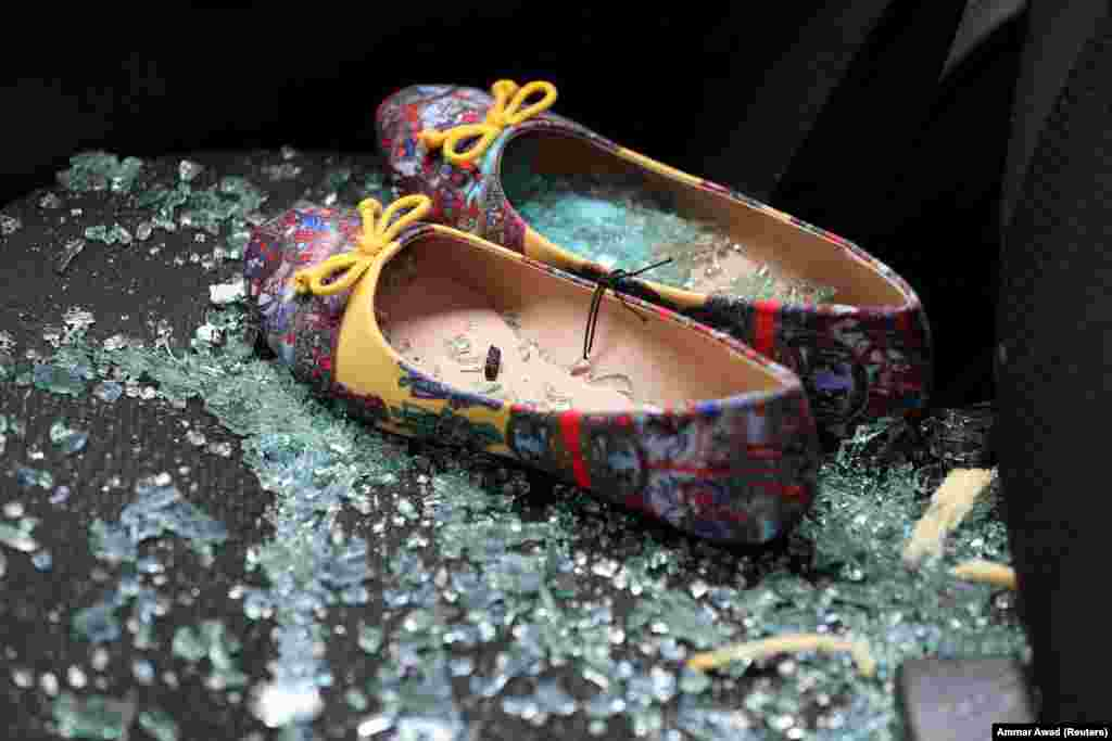 Shattered glass covers shoes left on the seat of a car that was damaged after a rocket hit a house north of Tel Aviv, Israel, on March 25. (Reuters/Ammar Awad)