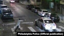 Полиция көлігіне қарата оқ атып тұрған ер адам, Филадельфия, АҚШ. 7 қаңтар 2015 жыл.