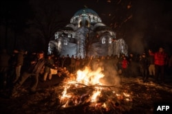 People attend a ceremonial burning of badnjak on Christmas Eve in front of St. Sava's cathedral.