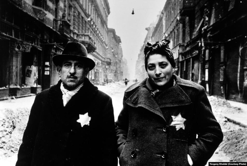 """Эту семейную пару Евгений Халдей встретил в январе 1945 года в будапештском гетто, вскоре после того, как квартал был освобожден от нацистов. Халдей был поражен тем, что даже после освобождения города мужчина и женщина продолжают носить нашитые по приказу оккупантов шестиконечные звезды. Пара поначалу испугалась фотографа, но он поздоровался с ней, как он сам говорит, на """"немецко-еврейском языке"""", после чего сорвал звезды с их одежды."""