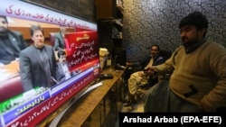 People watch a TV broadcast of Pakistani Prime Minister Imran Khan addressing the Parliament on February 28.