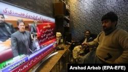 Люди смотрят выступление премьер-министра Пакистана Имрана Хана в парламенте, 28 февраля 2019 года.