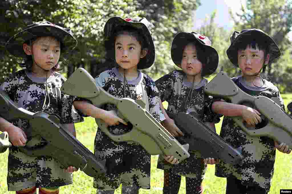 Chinese children, holding toy guns, participate in an event to simulate military training at a children's activity center in Shenyang, in Liaoning Province. (Reuters/Stringer)