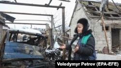 A local woman reacts near her house, damaged during recent shelling, in the village of Novoluhanske in Donetsk region on December 20.
