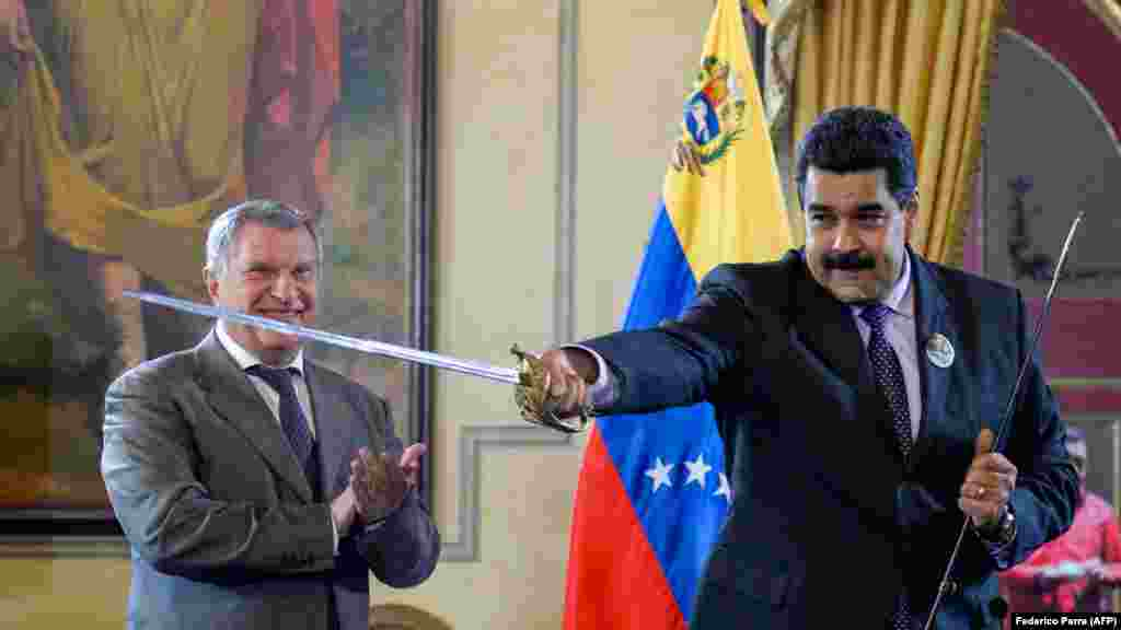 Venezuelan President Nicolas Maduro (right) holds a sword, given as gift by Russian oil company Rosneft CEO Igor Sechin, during the signing of agreements at the Miraflores presidential palace in Caracas on July 28. (AFP/Federico Parra)