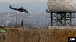 Syria -- A helicopter flies near a radar at the Russian Hmeimim military base in Latakia province, in the northwest of Syria, December 16, 2015