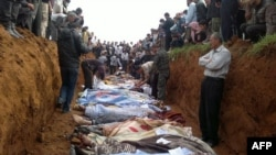A picture released on April 6 by the opposition Local Coordination Committees in Syria (LCC) purportedly shows people standing around a mass grave in the town of Taftnaz.