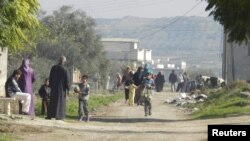 Residents flee their homes after shelling by government forces at Houla, near Homs, in early December.