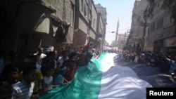 Demonstrators hold a giant flag as they march through the streets of Damascus