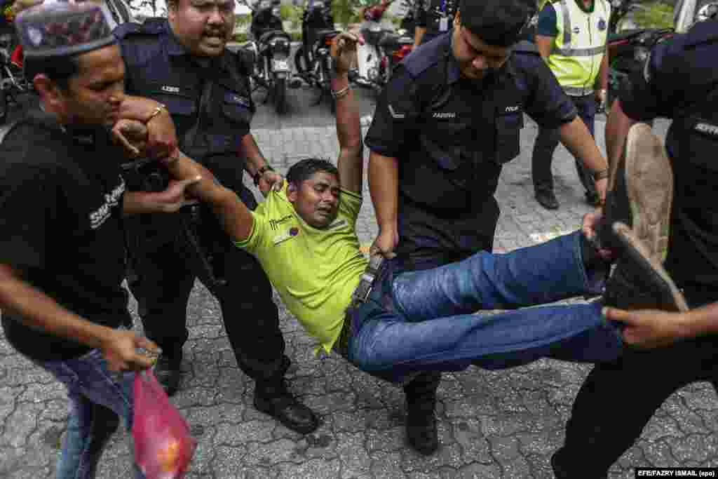 Royal Malaysia Police officers detain a Rohingya Muslim protester from Burma during a demonstration in Kuala Lumpur, Malaysia.