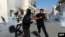 Bahrain -- Protestors run for cover after police fired tear gas canisters to disperse them in the village of Diraz, 14Feb2011