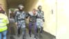 ОМОН кызматкерлери Москвадагы митингдердин катышуучусун кармап кетип жаткан учур.