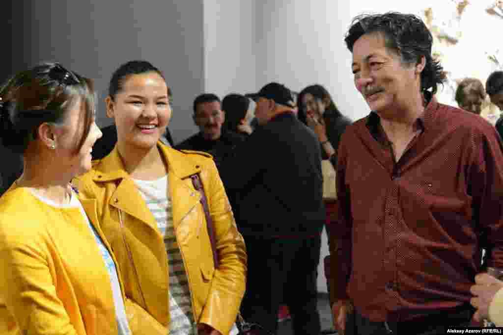 Рашид Нурекеев (на этом фото он беседует с посетительницами выставки) – известный казахстанский художник, творящий в жанре современного искусства. Но, несмотря на свою известность и признание в профессиональной среде, с персональными выставками к зрителям он выходит редко. Предыдущая проходила десять лет назад. Существует мнение, что галереи опасаются предоставлять Нурекееву пространство под выставку из-за его слишком критического взгляда на казахстанскую действительность. Чаще всего его работы можно увидеть на групповых выставках.