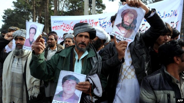 Afghan men in Herat shout anti-Iran slogans as they display pictures of their family members who have allegedly been killed by Iranian forces on December 9.