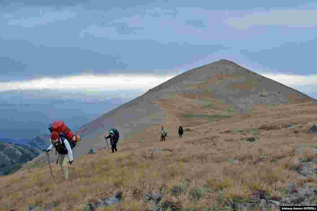 Группа, пройдя траверсом по склону горы Рахат (возвышается сзади), приближается к подножию горы Кыземшек.