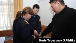 Полицейские снимают наручники с Аскара Молдашева в зале Бостандыкского районного суда. Алматы, 1 марта 2013 года.