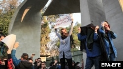 Iranian students clash with riot police during an anti-government protest around the University of Tehran on December 30