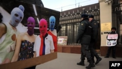 A supporter of the female punk band Pussy Riot holds a photo of a band while he and others picket police headquarters in Moscow on March 8.